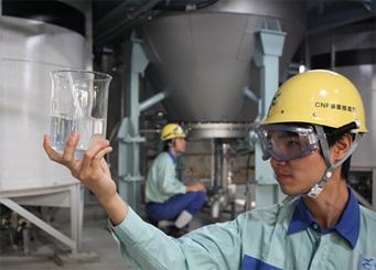 CNF 分散液(ビーカー内)と実証生産設備